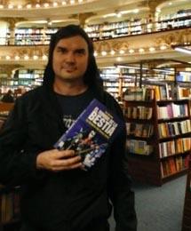 O autor posa com uma de suas publicações
