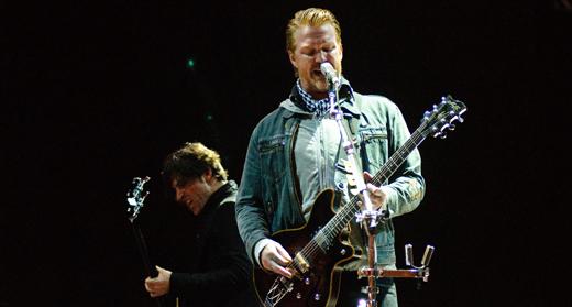 O cara: Josh Homme canta e destrói sua guitarra, com o baixista Michael Shuman agitando no fundo