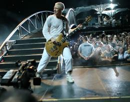 O baixista evolui na passarela, no meio do público