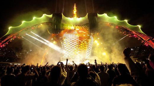 Visão geral do palco no momento em que o telão se desmembras e desce ao piso, encobrindo os músicos