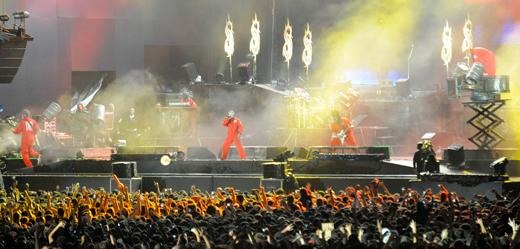 Vista geral do palco no início do show: kit de percussão é erguido do lado direito e fogos explodem