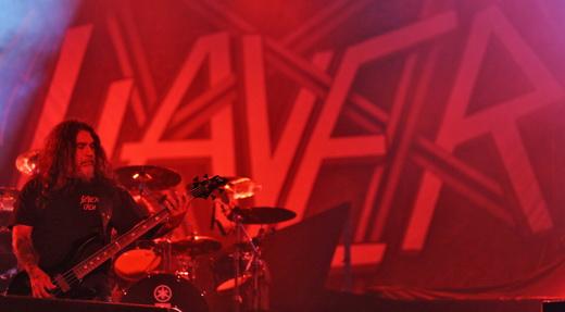 O baixista e vocalista Tom Araya, meio paradão, com o mundo pintado de vermelho do Slayer ao fundo