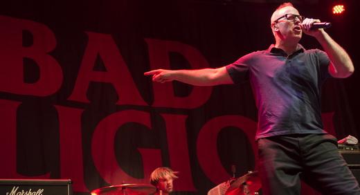 Greg Graffin aponta para o pano de fundo com o logotipo do Bad Religion: 29 músicas em 1h20 no gás