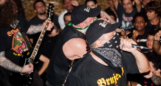 Os vocalistas tex mex El Brujo e Fantasma se jogam na beirada do palco, sobre o público do Odisséia