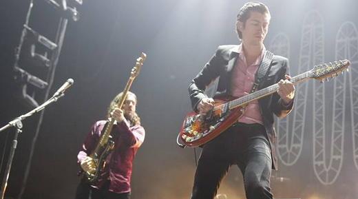 O baixista Nick O'Malley, que usaria uma calça zebrada no bis, e Alex Turner esmerilhando a guitarra