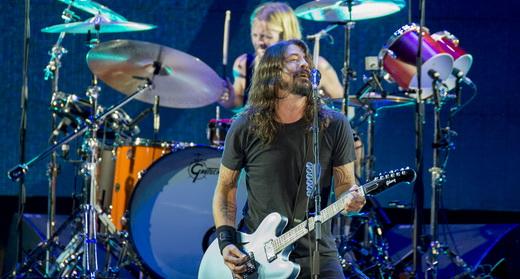 Dave Grohl canta e toca guitarra no início do show do Foo Fighters, com o batera Taylor Hawkins ao fundo