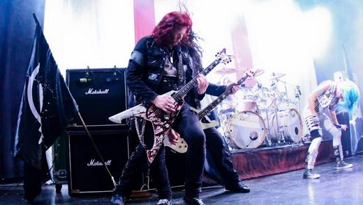 Michael Amott e o baixista Sharlee D'Angelo agitam, com Alissa batendo cabeça no centro do palco