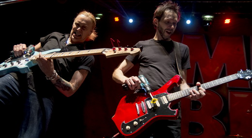 O baixista Billy Sheehan e o guitarrista Paul Gilbert usam furadeiras no duelo na beirada do palco