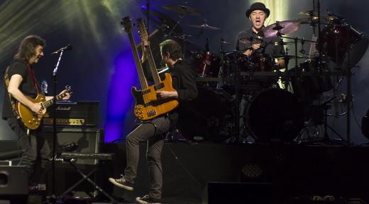 Steve Hackett agitando com o baixista Lee Pomeroy e sua double neck, e o baterista Gary O'Toole