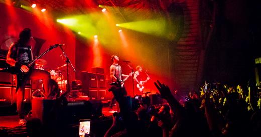 Vista lateral do palco do Bullet For My Valentine, com o público jovem enlouquecendo no meio do salão