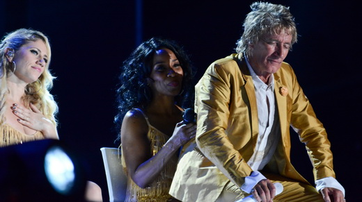 Rod aproveita o intervalo vocal para descansar sentando no colo de uma das belas vocalistas