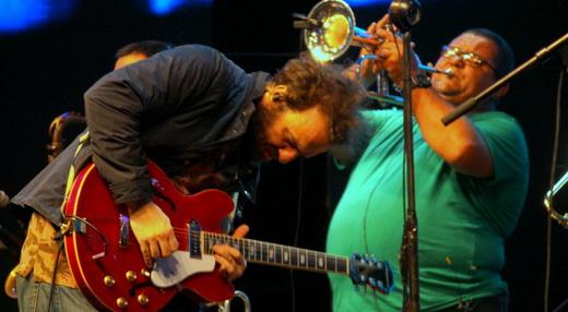 Marcelo Camelo concentrado na evolução instrumental de sua guitarra, na frente do trompetista Bubu