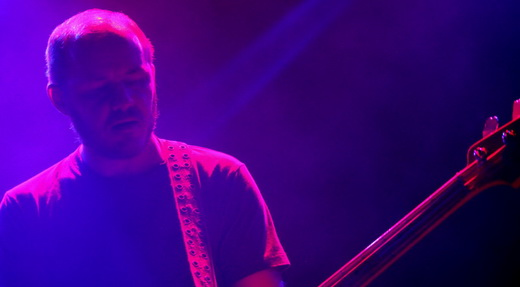Michael James, sempre no centro do palco, se divide entre o baixo e a guitarra como um mediador