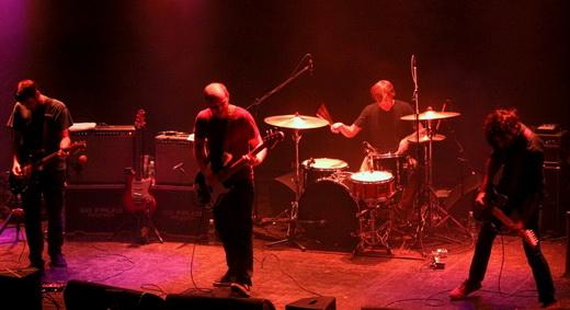 O guitarrista Mark Smith, Michael James e Munaf Rayani, com o baterista Chris Hrasky no fundo