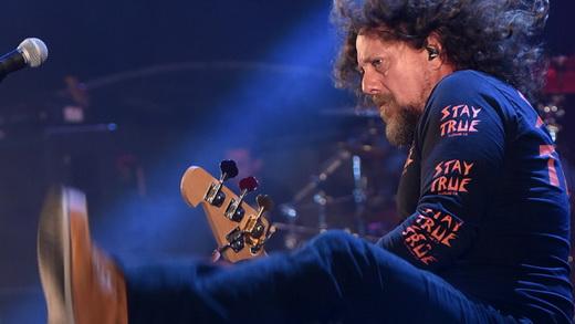 O baixista Canisso, figuraça com os cabelos esvoaçantes, tenta um salto durante o show do Raimundos