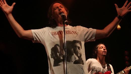 André Fratesqui canta com a camiseta lançada ao palco pelo público; no fundo o baixista Mauro Berman