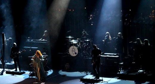 Plano geral do palco, com os músicos na penumbra e Florence Welch e suas vestes em destaque