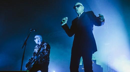 O estático Andrew Eldritch com o microfone em punho, ao lado do guitarrista Chris Catalyst