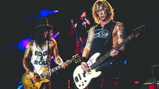 O guitarrista Slash em plena interação com o baixista Duff McKagan; Axl Rose aparece no fundo