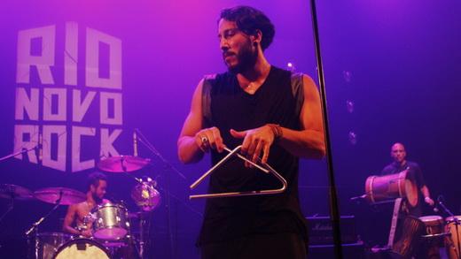O vocalista do Overdrive Saravá, Gregory Combat, tocando triângulo, entre bateria e percussão