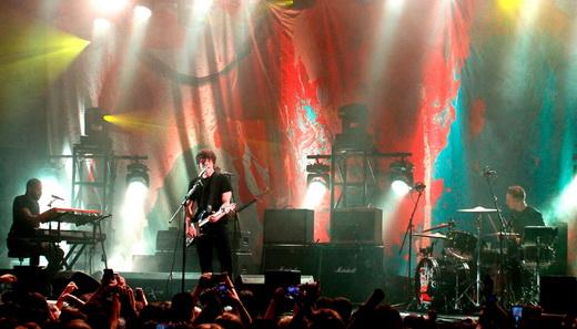 Vista principal do palco com Jake Bugg no centro e cenário e iluminação próprios dessa turnê