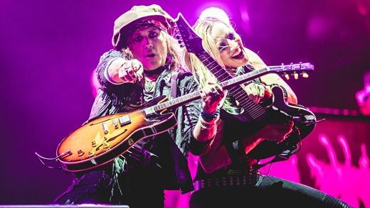 O guitarrista Ryan Roxie, que já foi da banda de Slash, junto com Nita Strauss na beirada do palco