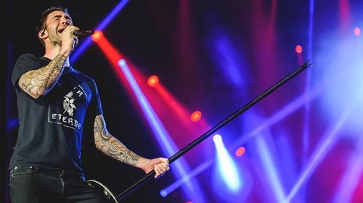 O vocalista do Maroon 5, Adam Levine, solta a voz, com o pedestal do microfone na mão