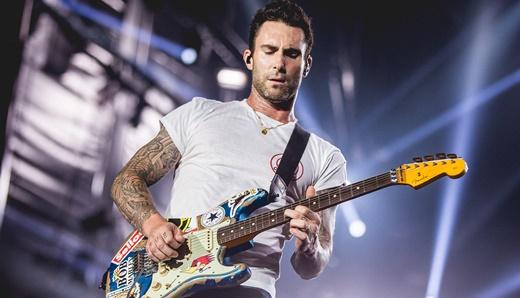 Adam Levine fazendo das suas com a guitarra a tiracolo; ele chega a duelar com James Valentine