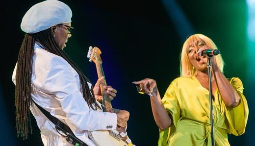 Kimberly, com típico figurino, banca a desafiante do peculiar modo de tocar guitarra de Nile Rodgers