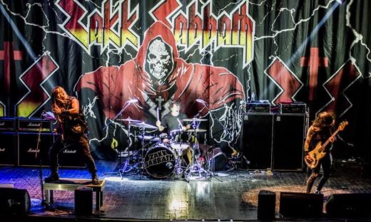 Zakk Wylde, Joey Castillo e Rob Blasko: o trio e os símbolos do Black Sabbath no fundo e na bateria