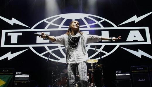 O vocalista do Tesla, Jeff Keith, com figurino discreto, de braços abertos tal qual o Cristo Redentor