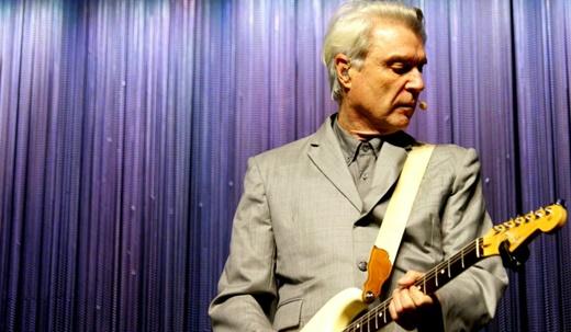 David Byrne tocan guitarra com o alinhado terno cinza, figurino de todos os 11 músicos do show