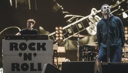 O jeito clássico de Liam encarar o microfone, na foto ao lado do tecladista Christian Madden