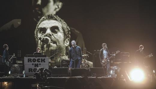 Vista geral do palco de Liam Gallagher, com toda a banda alinhada, e a imagem dele ampliada no telão