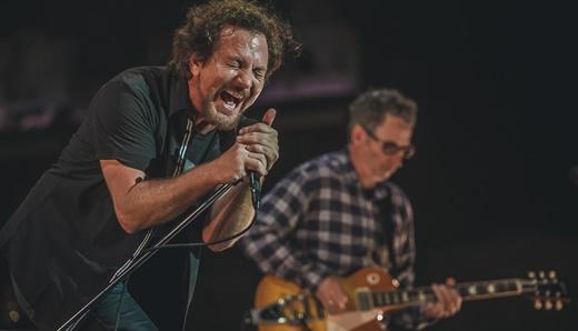 Eddie Vedder forçando a voz em sua performance, com Stone Gossard tocando concentrado, atrás