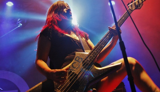 Mais animada na turma, a baixista de cabelos coloridos Jennifer Finch toca na beirada do palco