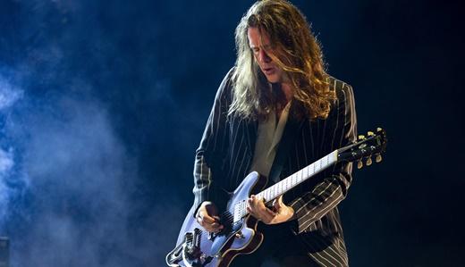 O guitarrista Jamie Cook, de certa forma ofuscado pelo reforço de outros quatro músicos no palco