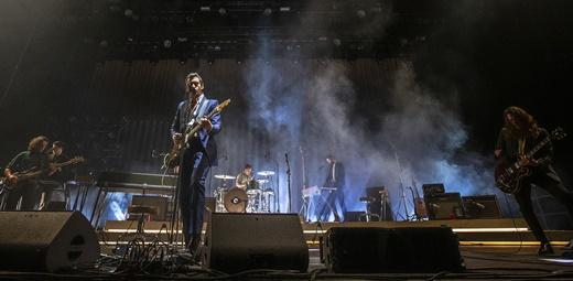 Vista do palco do Arctic Monkeys com os músicos de apoio e Alex Turner no comando da banda