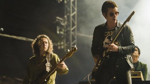O baixista Nick O'Malley, Alex Turner e um dos músicos de apoio tocando teclados no fundo