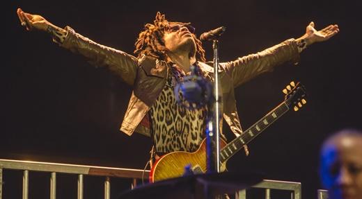 Lenny Kravitz ergue os braços em cima da plataforma, no início do show: deixe o amor reinar