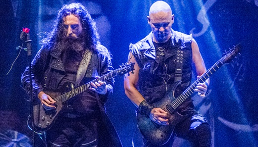 Os guitarristas Richard Shaw e Marek Smerda tocam juntos em coreografia na beirada do palco