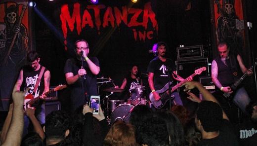 Vista geral do palco do Matanza Inc, com o pano de fundo e as laterais baseados no álbum de estreia