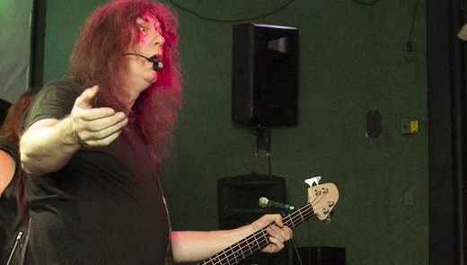 O baixista e vocalista do Raven, John Gallagher, microfone acoplado ao rosto, interage com a plateia
