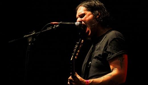 O guitarrista e vocalista do Molho Negro, João Lemos, se esgoelando antes de pular no meio do público