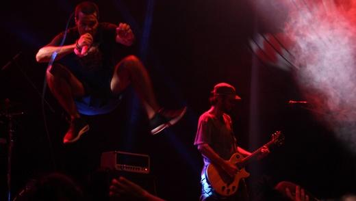 Rodrigo 'voa' em um de seus saltos atléticos, com o guitarrista Ric Mastria tocando à direita