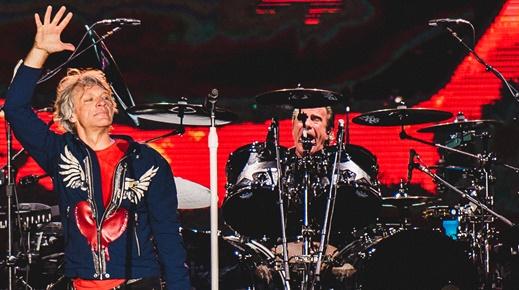 Jon Bon Jovi acena para o público no início do show, com o batera Tico Torres cantando ao fundo