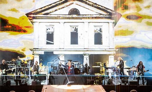 Vista geral do palco com a banda em ação e o telão no clipe de abertura de 'This House is Not For Sale'