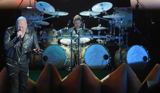 Michael Kiske em momento isolado; ao fundo, Daniel Löble e a bateria de quatro bumbos vibrantes