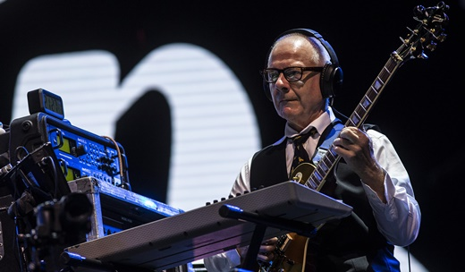 Mentor do King Crimson, Robert Fripp toca guitarra com fones de ouvido, diante de equipamentos