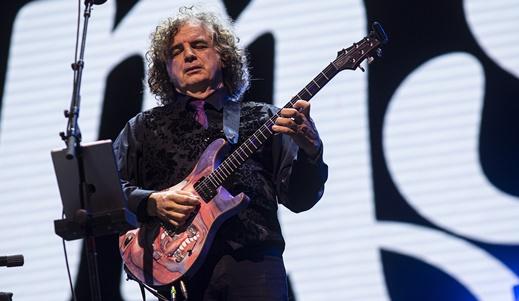 Jakko Jakszyk canta  e toca a guitarra com a imagem da capa do 'disco da boca' estampada